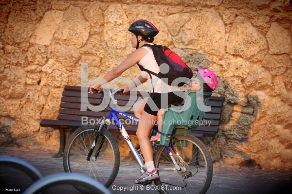 Woman Riding Bicycle with Daughter