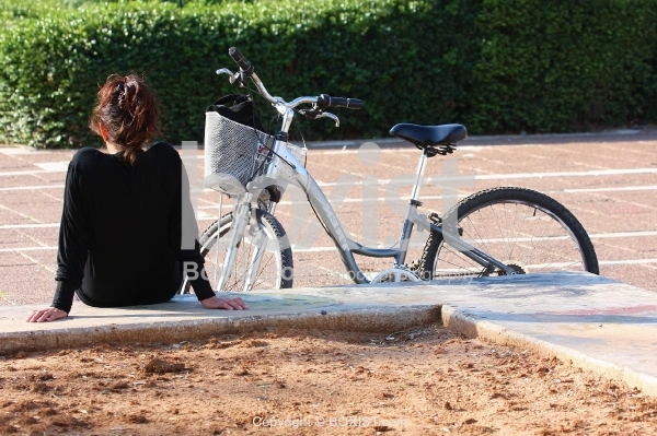 Woman Waiting with Her Bicycle
