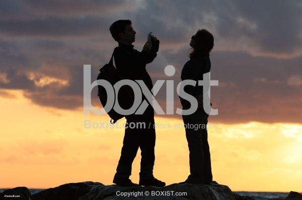 Couple Taking Pictures at Sunset