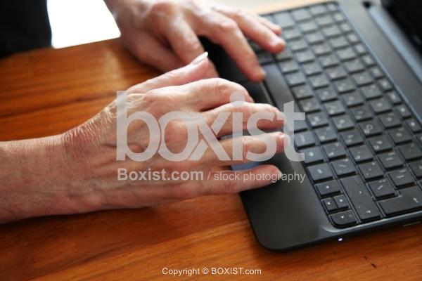 Elderly Man Hands Typing on Computer Keyboard