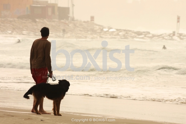 Man and His Dog on the Beach Shore