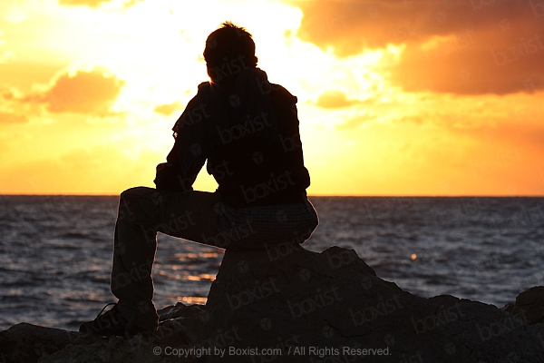Man Sitting and Watching Sunset