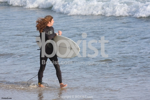 Surfers Walking Along the Beach