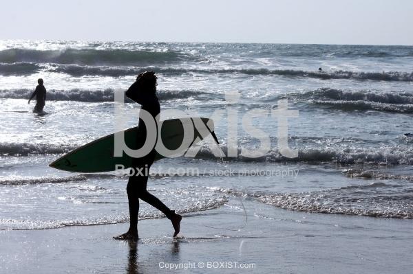 Surfer Walking on Sea Shore