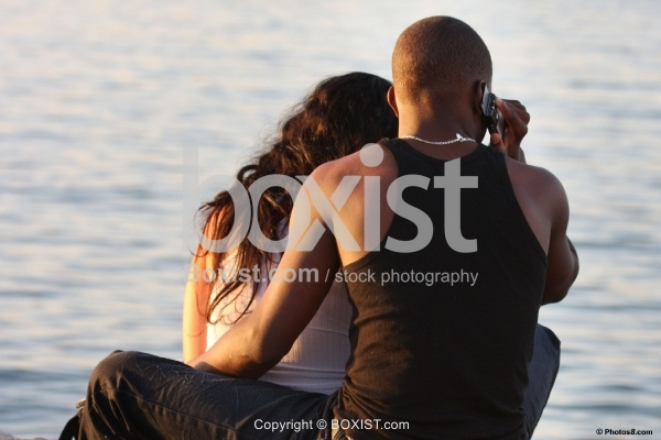 Romantic Young Couple Sitting By The Sea