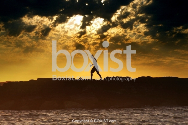 Man Silhouette Walking on Sea Rocks at Sunset