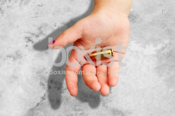Little Girl Hand Holding A Bullet
