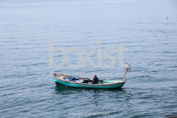 Man Sitting In Small Fishing Boat