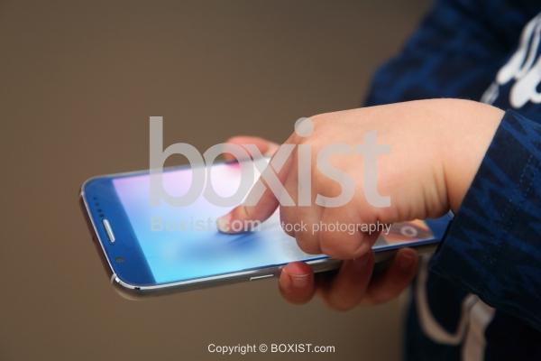 Child Hand Touching Smartphone Screen