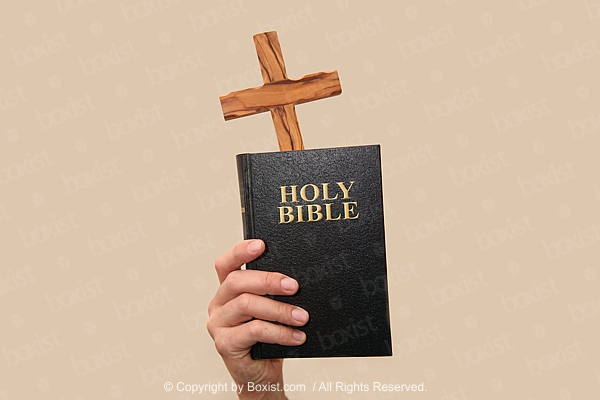 Hand Holding Holy Bible Book