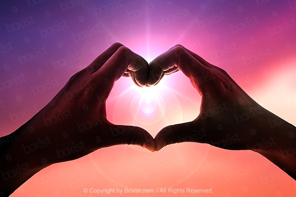 Making Heart With Hands Over The Sun