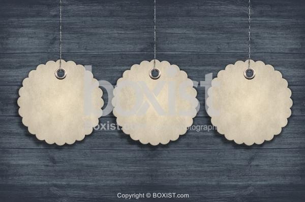 Three Circular Tags Hanging On Wood Wall