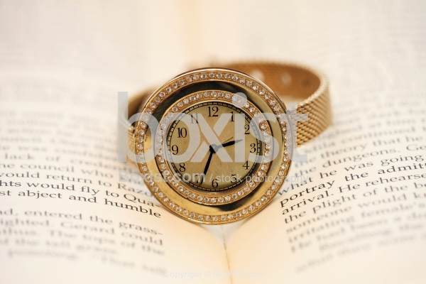 Hand Watch On Top Of Open Book