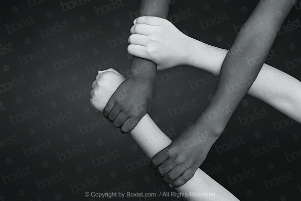 Black And White Children Four Hands Crossed Together On Black Background