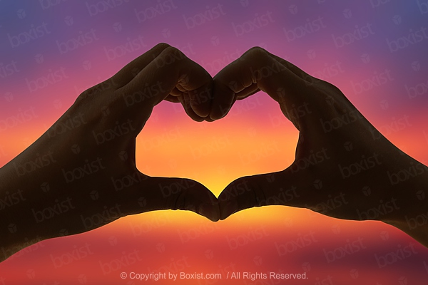 Silhouette Of Love Heart Symbol Shaped By Two Hands At Sunset